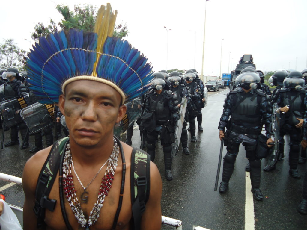 An indigenous leader stares into the camera with rows of police in riot gear standing behind him.