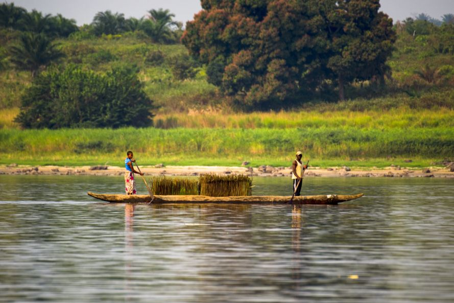 A man and woman in a boat, fishing on the Congo river.